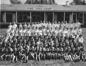 Large Group of campers and staff post outside dining hall in historical photo from Pine Tree Camp