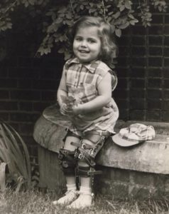 Historical photo of girl with polio in leg bracessitting on rock wall