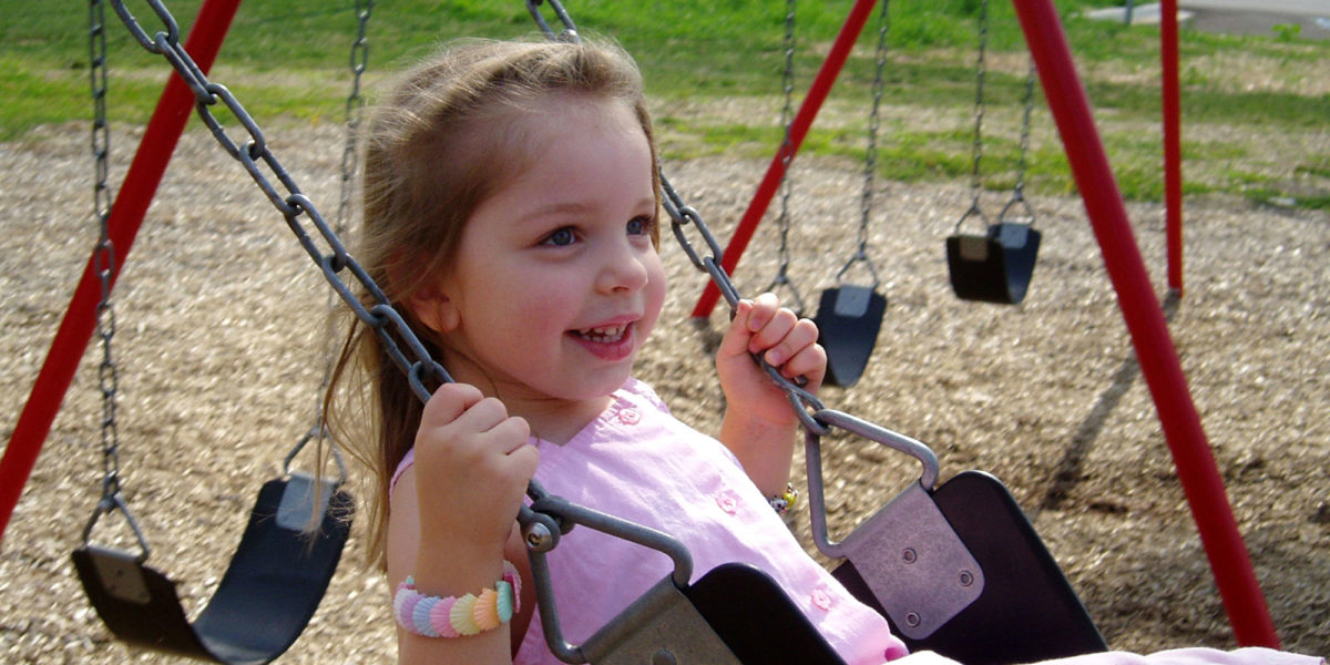 Little girl swings on playground