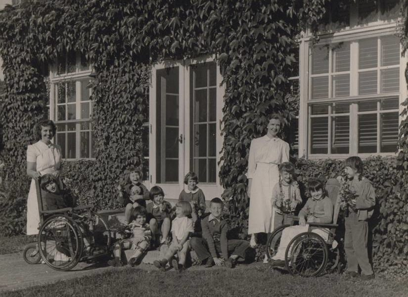 Nurses pose with group of children outside old Hyde Home in historical photo