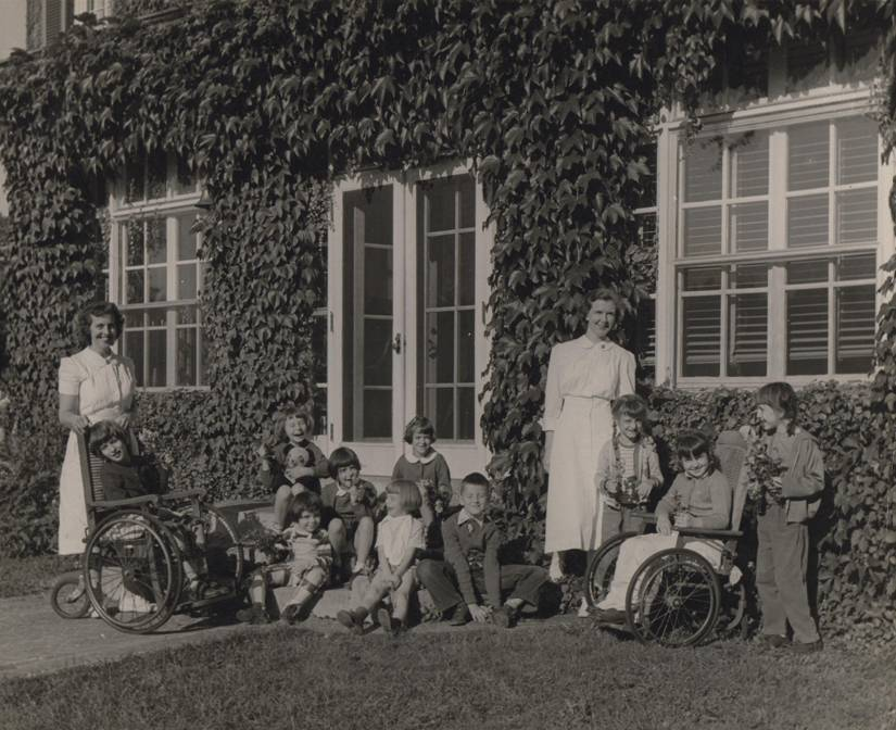 Nurses pose with group of children in historical photo outside Hyde Home