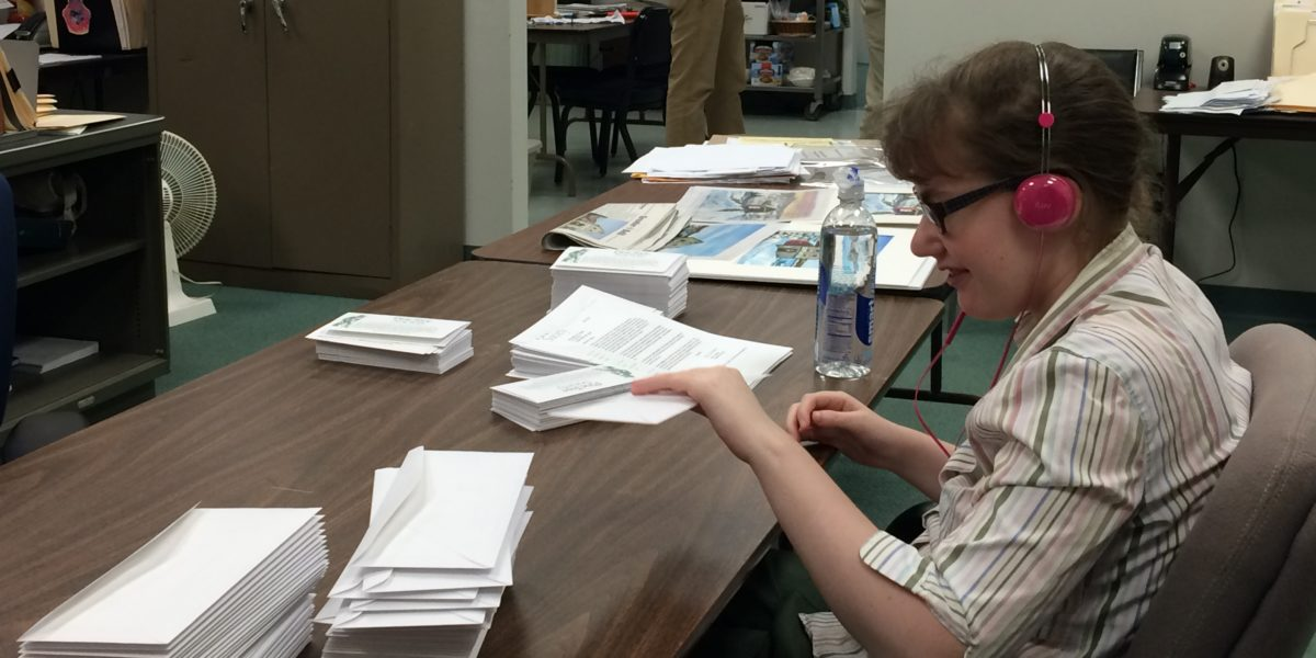 Client of Pine Tree Society Career Development program works on mailing project in office