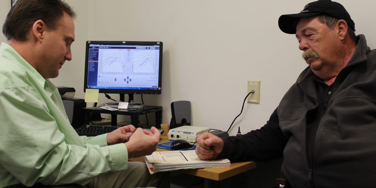 Audiologist at Pine Tree Society talks to client