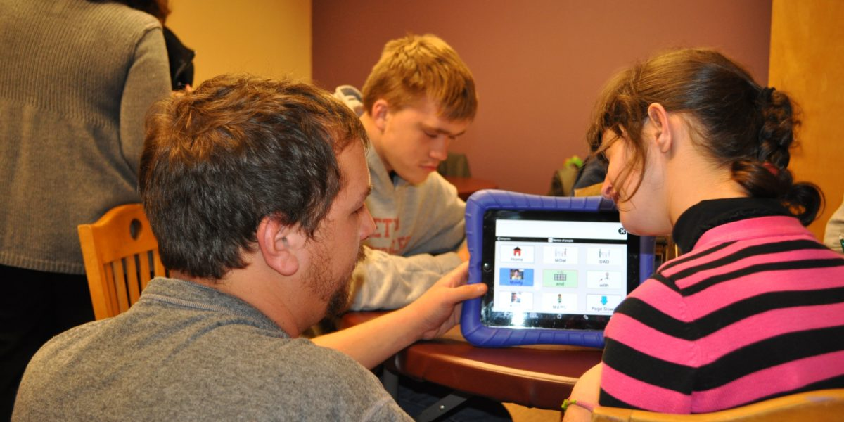 Pine Tree Society staff helps person communicate with assistive technology