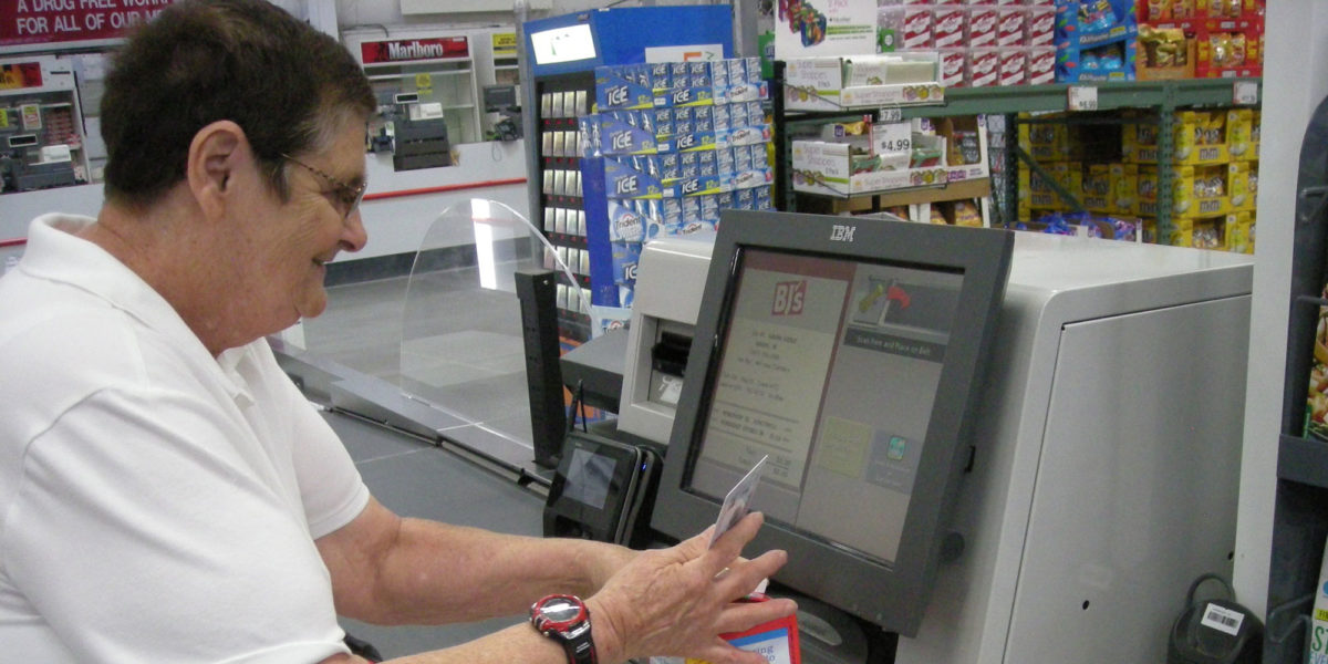 Pine Tree Society Home Support client uses self checkout kiosk at store